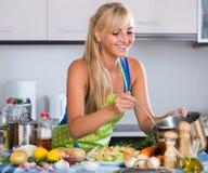 Cheerful  blondie preparing veggies in domestic kitchen Royalty Free Stock Image