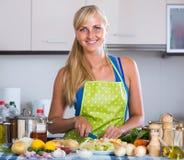 Cheerful  blondie preparing veggies in domestic kitchen. Cheerful long-haired spanish blondie preparing veggies in domestic kitchen Stock Photography