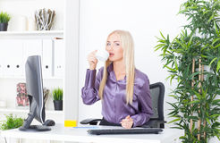 Cheerful blounde female having a coffee break in the office Stock Images