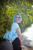 Cheerful blue-haired girl student with a briefcase of silver material. One strolls through the park royalty free stock photography