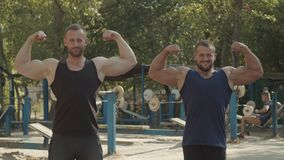 Cheerful bodybuilders showing double biceps pose