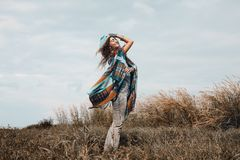 Cheerful boho woman wearing poncho on field Royalty Free Stock Photography