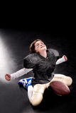 Cheerful boy american football player sitting with ball and triumphing stock images