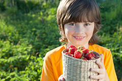 Cheerful boy with a basket of berries Royalty Free Stock Image