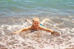 Cheerful boy bathes in the sea waves royalty free stock images