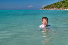 Cheerful boy bathes in the tropical sea, sunny day. Cute child swimming in turquoise clear water. Concept of vacation at the sea. royalty free stock image