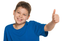Cheerful boy in blue shirt holding his thumb up Stock Photography