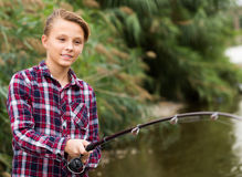 Cheerful boy casting line for fishing on lake Royalty Free Stock Images
