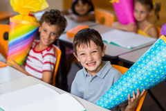 Cheerful boy with classmates holding craft item Royalty Free Stock Photo