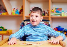 Cheerful boy with disability at rehabilitation center for kids with special needs, solving logical puzzle Royalty Free Stock Image