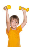 Cheerful boy do exercises with dumbbells Stock Photo