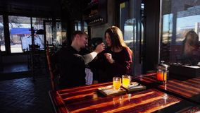 Cheerful boy feeding girlfriend at cafe. Jocund guy feeding pretty girlfriend at cafe. Boy in dark sweater and happy girl sitting at table and resting. Concept stock video footage