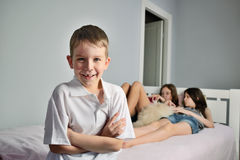 Cheerful boy foreground in the room whith girls Royalty Free Stock Image