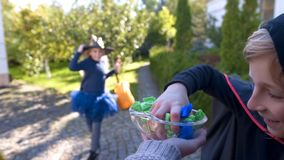 Cheerful boy and girl in costumes taking candies from plate, happy childhood stock photography