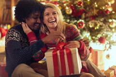 Cheerful boy and girl exchanging Christmas presents stock images