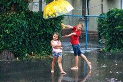 Cheerful boy and girl with umbrella during summer rain. Children enjoy the warm rain . Walk in the rain royalty free stock image
