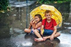 Cheerful boy and girl with umbrella during summer rain. Children enjoy the warm rain . Walk in the rain stock photo