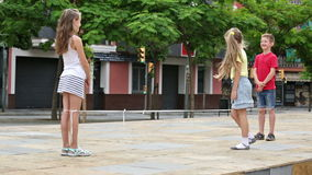 Cheerful boy and girls having fun. Cheerful boy and girls in elementary school age having fun with chinese jumping rope stock video footage