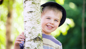 Cheerful boy hiding himself in the garden Royalty Free Stock Image