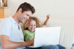 Cheerful boy and his father using a laptop. In their living room royalty free stock image