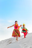 Cheerful boy and his happy mother running on sand Stock Images