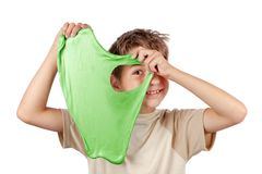 Cheerful boy holding a slime and looking throw its hole. Studio. Cheerful boy holding a green slime and looking throw its hole. Studio isolated on white royalty free stock photos