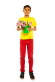 Cheerful boy holding pail with pink tulips. Cheerful boy in red jeans holding pail with pink tulips on the white background stock photography