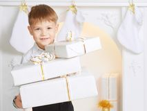Cheerful boy holds a lot white boxes gift on the background of t. Cheerful boy holds a lot many boxes gift on the background of the fireplace and the stockings Stock Photos