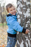 Cheerful boy hugging birches, autumn park Stock Photography