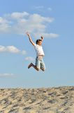 Cheerful boy jumping on sand Royalty Free Stock Photo
