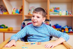 Cheerful boy with disability at rehabilitation center for kids with special needs, solving logical puzzle Royalty Free Stock Photos