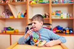 Cheerful boy with disability at rehabilitation center for kids with special needs, solving logical puzzle Stock Photos