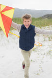 Cheerful boy with kite at beach Stock Images