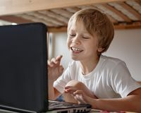 Cheerful boy with laptop. Positive cheerful young boy working with modern laptop at home Stock Photos