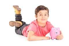 Cheerful boy laying on the floor and holding a piggybank Stock Photo