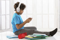 Cheerful boy listening to  Music with the Books Stock Photography
