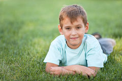 Cheerful boy lying on the lawn Royalty Free Stock Photos