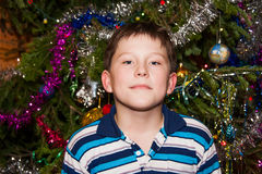 Cheerful boy near a Christmas tree Royalty Free Stock Photos