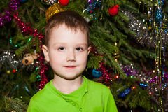 Cheerful boy near a Christmas tree Royalty Free Stock Images