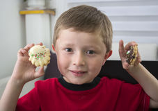 Cheerful boy offering you a chocolate cookie. Royalty Free Stock Image