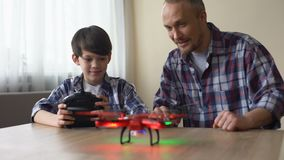 Cheerful boy operating drone with remote control, dad catching quadcopter, fun stock footage