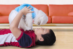 Cheerful boy playing with dog at home Royalty Free Stock Photography