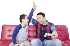 Cheerful boy playing video game with dad Royalty Free Stock Image