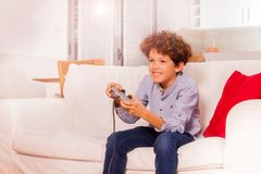 Cheerful boy playing video game in the living room. Portrait of cheerful schoolboy playing video game, sitting on the sofa in the living room Royalty Free Stock Photography