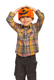 Cheerful boy with pumpkin hat. Holding hands on head isolated on white background Royalty Free Stock Image