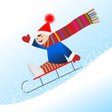Cheerful boy is rolling on a sledge from the mountain Stock Image