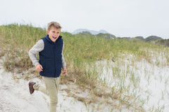 Cheerful boy running at beach Stock Photos