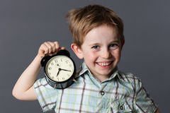 Cheerful boy showing an alarm clock for playful time concept Royalty Free Stock Photo