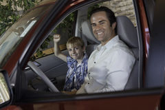Cheerful boy sitting in car with his father Stock Photos