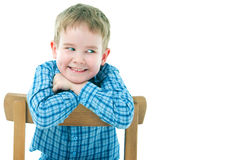 Cheerful boy sitting on a chair Stock Photos